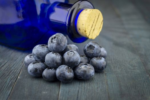 Fresh blueberries and corked blue glass pharmacy bottle on blue rustic board in close up