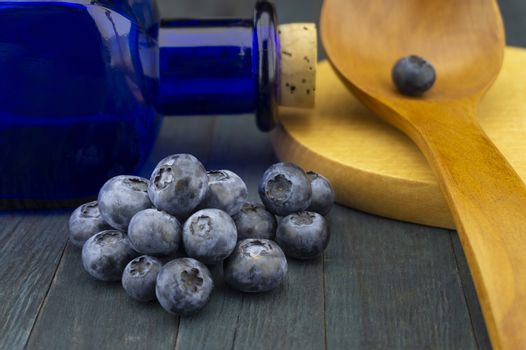 Food still life with fresh blueberries and wooden spoon with cutting board alongside a corked blue glass pharmacy bottle in close up