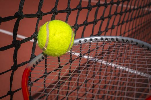 Tennis balancing ball on a racket alongside a net on a court in a sport and active healthy lifestyle concept