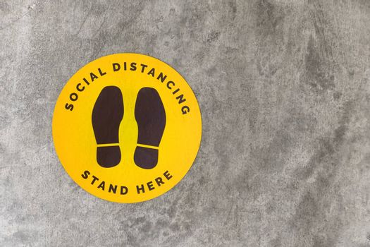 Top view footprint sign for stand in shopping mall, supermarket. Social distancing , COVID-19 comcept. Ccoronavirus crisis. yellow footprint sign with text caution social distance.