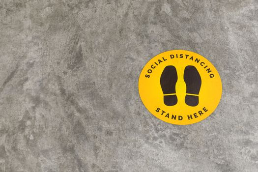 footprint sign for stand in shopping mall, supermarket. Social distancing , COVID-19 comcept. Ccoronavirus crisis. yellow footprint sign with text caution social distance.