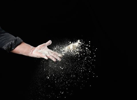 baker's male hand throws up a handful of white wheat flour on a black background, particles fly in different directions