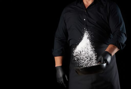 man in a black uniform holding a round cast iron pan with salt, the chef tosses white salt up on a black background