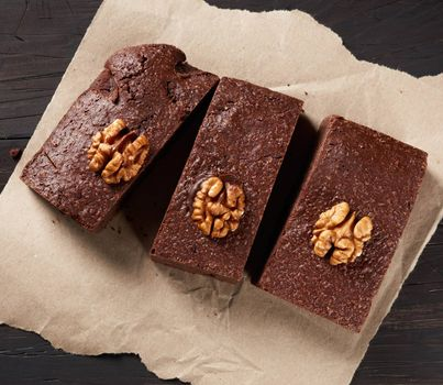 baked pieces of brownie chocolate cake with nuts on a brown piece of paper, top view, delicious dessert