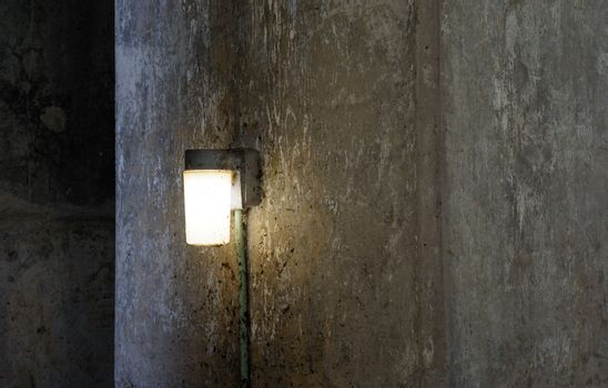 Light fixture on filthy cement wall.