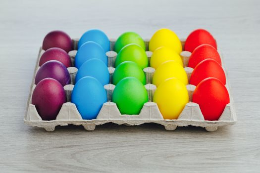 Easter festive multicolor eggs carton, light gray wooden background, close-up view