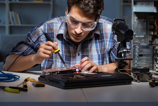 Young repair technician soldering electrical parts on motherboar