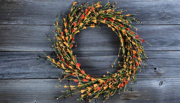 Seasonal autumn wreath with small orange flowers on vintage wooden background