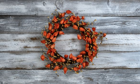 Seasonal autumn wreath with orange bell flowers on white rustic wooden background