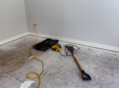Renovation of home floor with exposed plywood and working tools