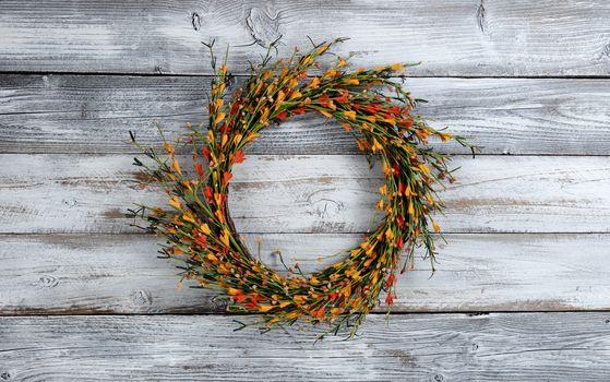 Seasonal autumn wreath with small orange flowers on white vintage wooden background