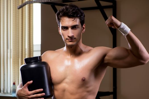 Man with nutrient supplements in sports gym