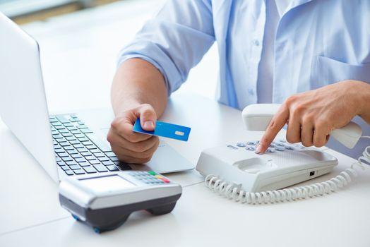 Man processing credit card transaction with POS terminal