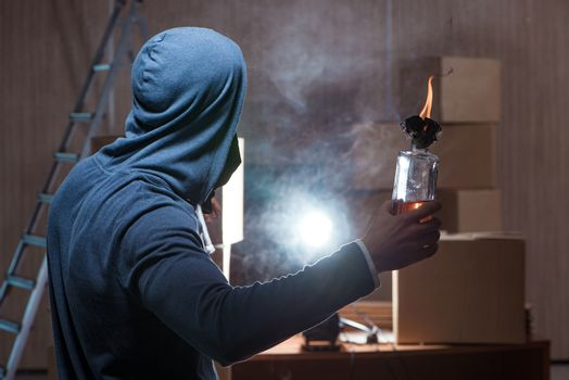 Rebel with molotov cocktail in dark room