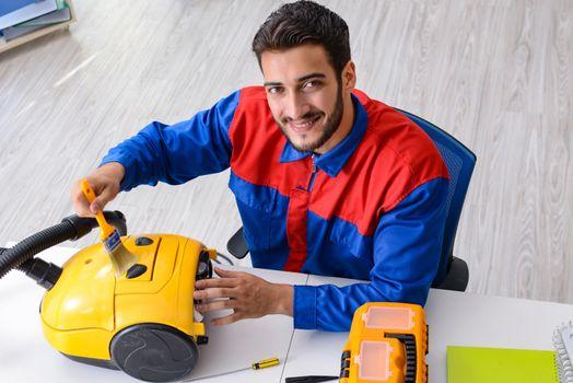 Man repairman repairing vacuum cleaner at service center