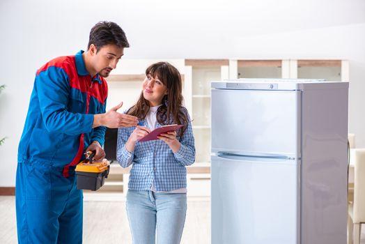 Man repairing fridge with customer