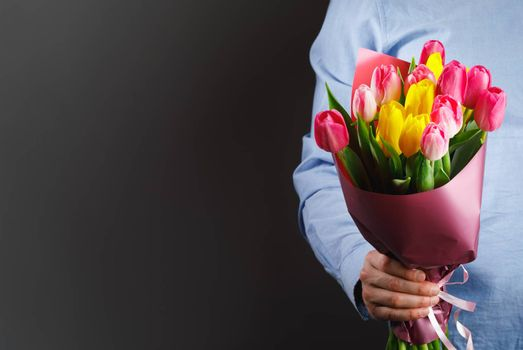 tulip flowers bouquet in hand, gray background with copy-space