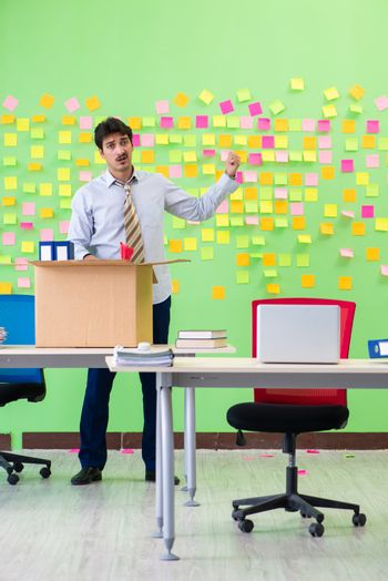 Man collecting his stuff after redundancy in the office with man