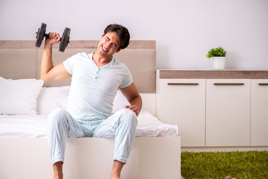Young man doing morning routine in bedroom