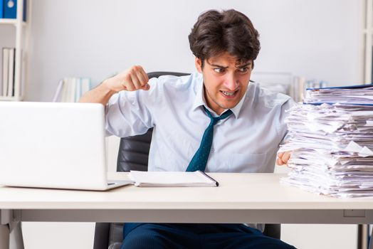 Overloaded busy employee with too much work and paperwork