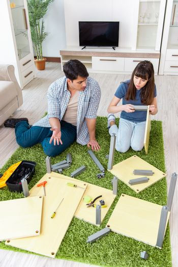 Young family assembling furniture at new house