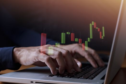 Business and technology concept  Close up businessman hands with laptop and candlestick chart background. Businessman hands use computer network control trade buy and sell stock market