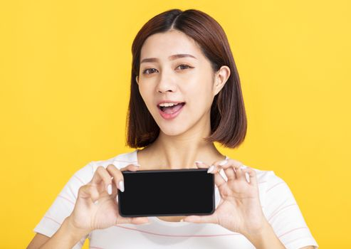 happy young woman showing blank screen mobile phone