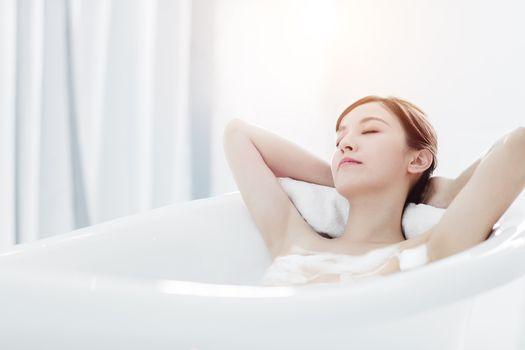 Beautiful young asian woman relaxing in bathtub
