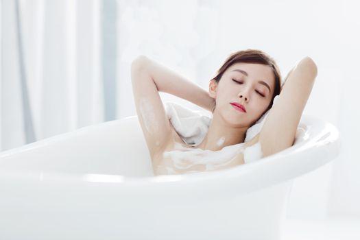 Beautiful young woman relaxing in bathtub