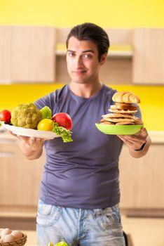 Man having hard choice between healthy and unhealthy food