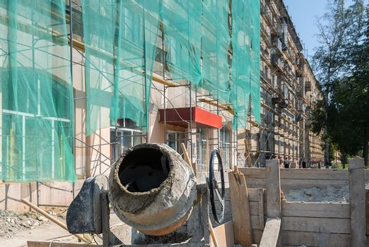 an industrial construction concrete mixer and a box of cement stand on the street against the background of a multi-storey building where the facade is being repaired