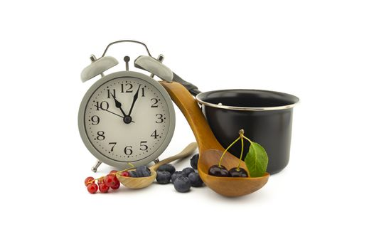 Culinary still life with old-fashioned alarm clock, pot, wooden spoons, cherries, red currants and blueberries over an off white background with copy space
