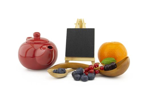 Fresh seasonal fruit still life with small chalkboard and assorted berries including blueberries, cherries and red currants on wooden spoons with orange and colorful red teapot