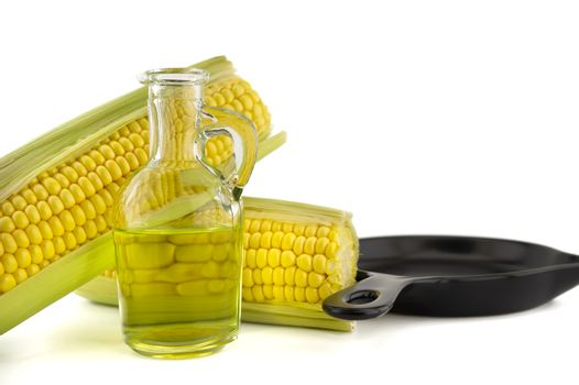 Corn oil in decanter and fresh corncobs next to the cast iron skillet isolated on white background with free copy space for text