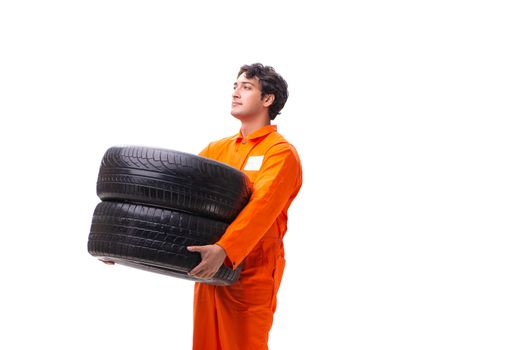 Young garage worker with tyre isolated on white