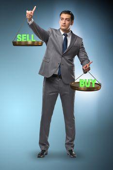 Businessman choosing between buying and selling
