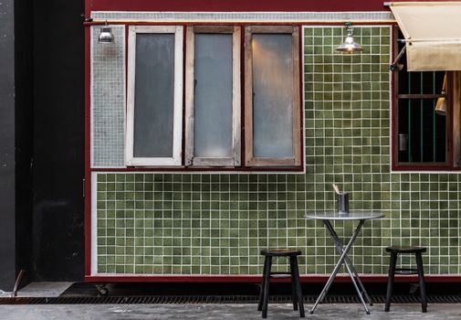 Table and wooden chairs in front of a traditional Chinese food shop. Concept and design front of Chinese retro style. No focus, specifically.