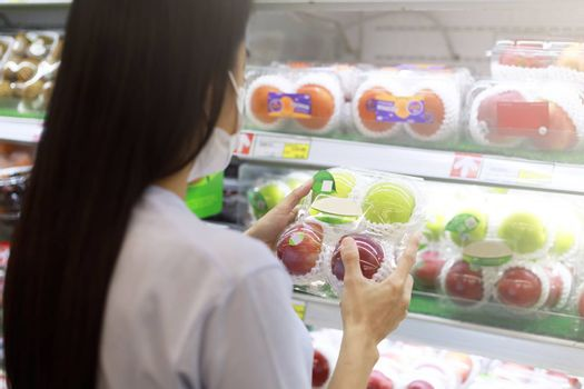 Women long hair wear protective face mask hands holding green and red apples ipackage. Asian female shopping at supermarket, Grocery to buy some food. New normal after covid-19 concept.