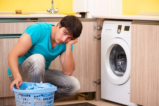 Young husband man doing laundry at home