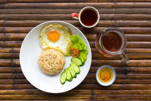 Scrambled egg, rice, fresh vegetables on white plate, sauce, jug and cup with tea on brown bamboo table. Thailand breakfast. Top view.