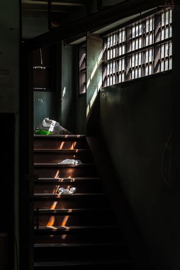 Light shines through the vent shade to wooden staircase in abandoned house was left to deteriorate over time. Selective focus.