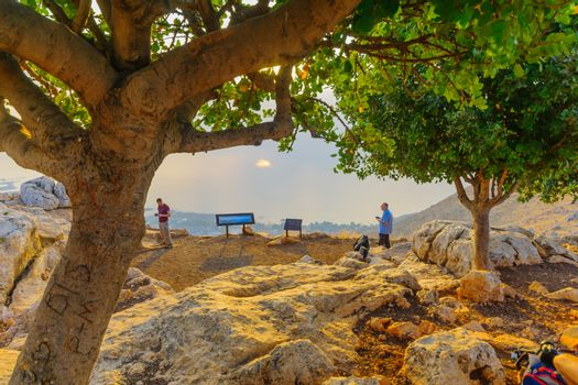 Arbel, Israel - August 14, 2020: View of the Sea of Galilee lookout in Mount Arbel National Park, at sunrise, with visitors. Northern Israel