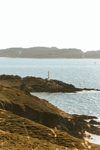 A long distance view of a white lighthouse on the coast