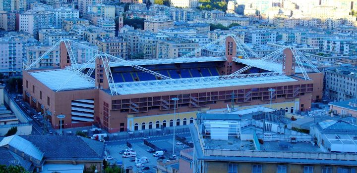 Genoa, Italy – August 5, 2020: Aerial view of shipping and container terminal, stacked containers and loading dock side cranes in the port of Genoa, Magazzini del cotone and Porto Antico, sea