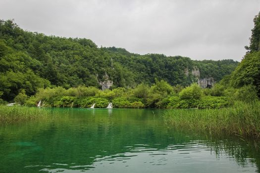 A view of a green lake over reeds with a waterfall and mountain in the background, Plitvice Lakes, Croatia