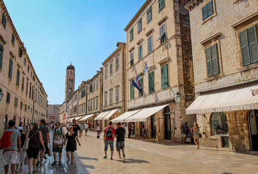 Dubrovnik, Croatia - July 15th 2018: The Stradun main street and shops in Dubrovnik's old town in summer, with the Zvonik Clock Tower, Croatia