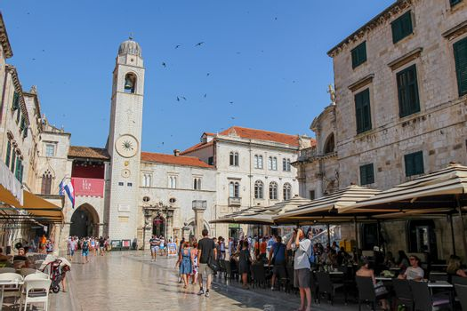 Dubrovnik, Croatia - July 15th 2018: The Stradun main street, cafe and clock tower in Dubrovnik's old town, with tourists in the summer, Croatia