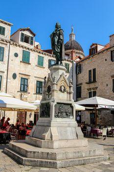 Dubrovnik, Croatia - July 15th 2018:The Spomenik Ivanu Gunduliću statue in Market Square, in the UNESCO World Heritage Site of Dubrovnik, Croatia