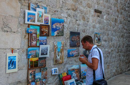 Dubrovnik, Croatia - July 15th 2018: A tourist eating ice cream, admiring artwork in Dubrovnik's historic old town in summer, Croatia