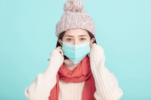 young woman in winter dress and wear medical mask